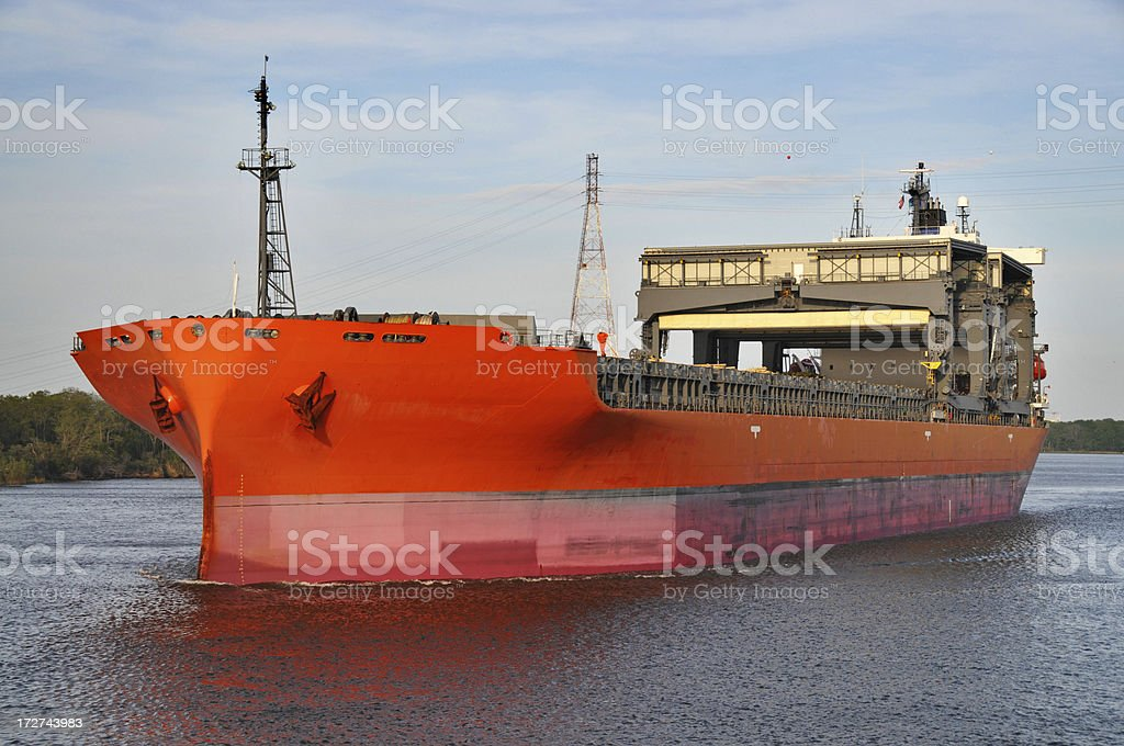 An orange ocean freighter on the water stock photo