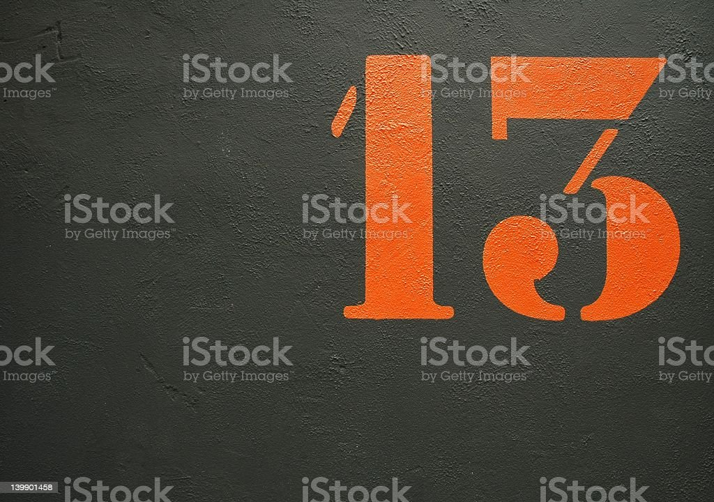 An orange stenciled number 13 on a black background royalty-free stock photo