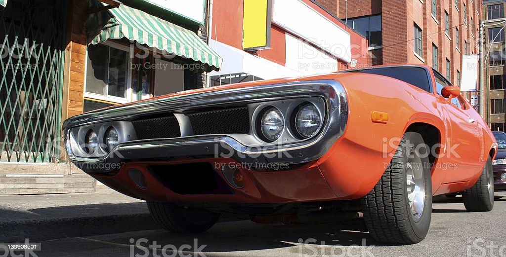 An orange vintage muscle car as seen from the ground stock photo
