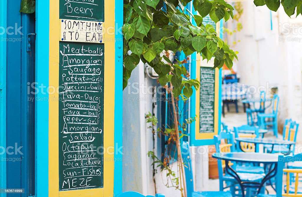 An outdoor cafe with blue chairs and menu chalkboard royalty-free stock photo