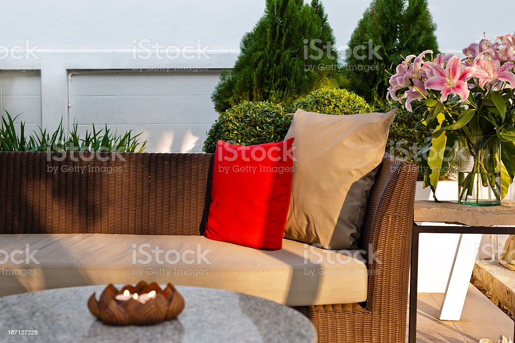 An outdoor patio sofa with accent pillows stock photo