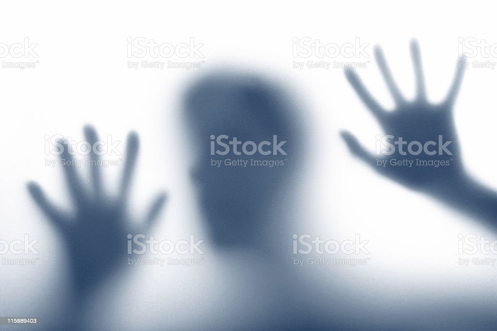 An outline of a person trapped behind a wall in royalty-free stock photo