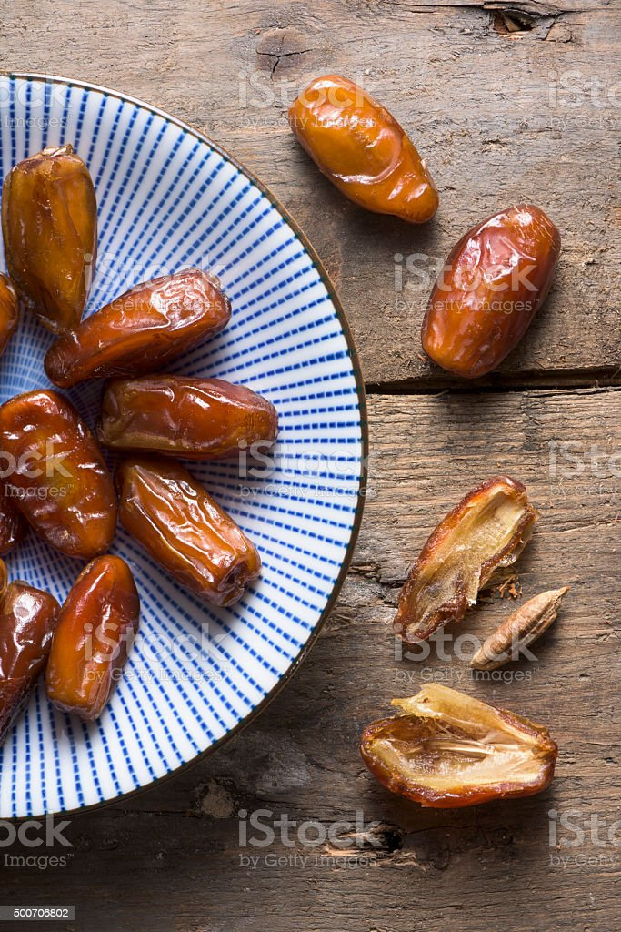 An overhead bowl of dates on a rough wooden background stock photo