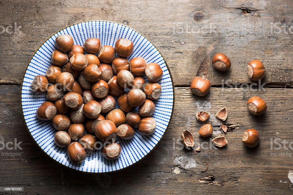 An overhead bowl of hazelnuts lying on a wooden background stock photo