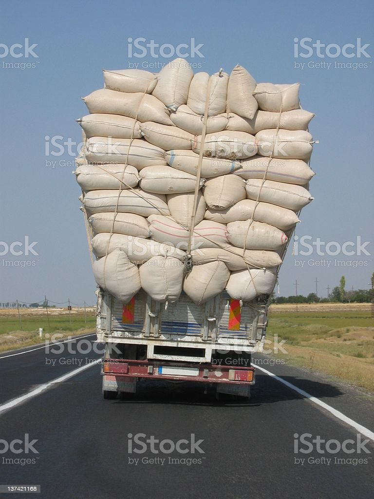 An overloaded truck leans to the side stock photo