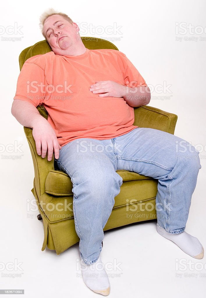 An overweight man sleeping in a chair with his shoes off stock photo