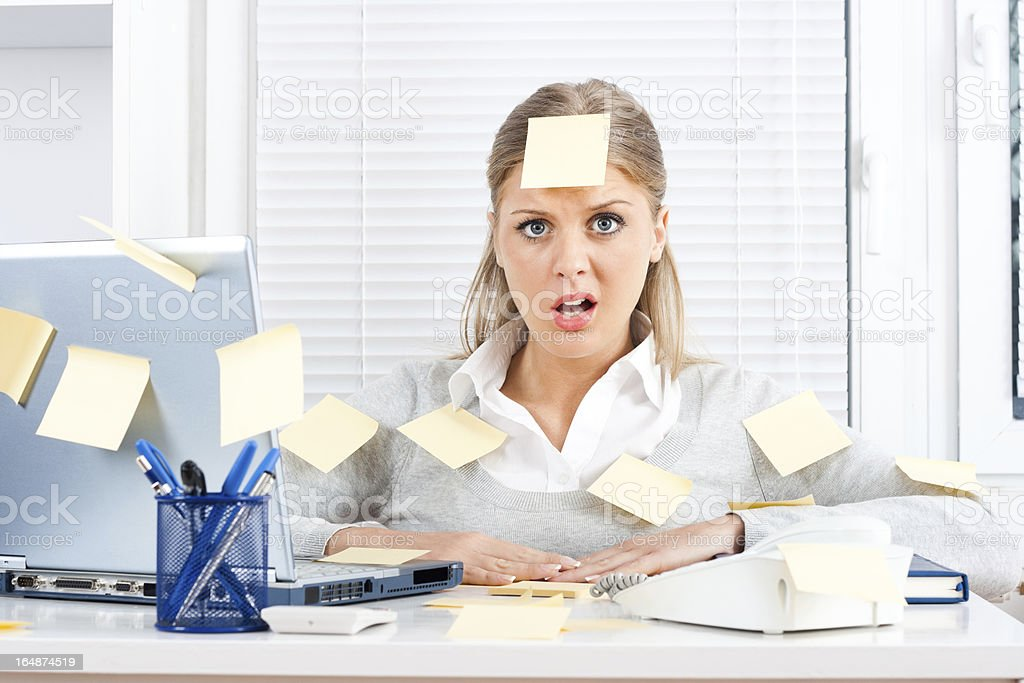 An overworked woman with sticky notes all over her and desk stock photo