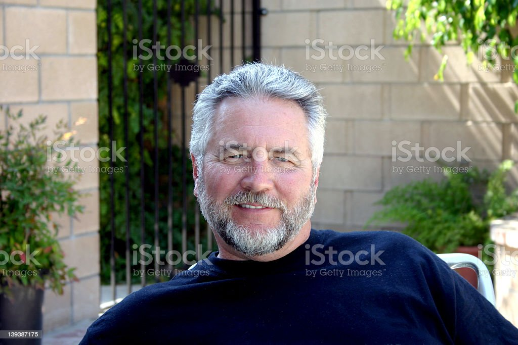 An senior man satisfied enjoying his early retirement stock photo