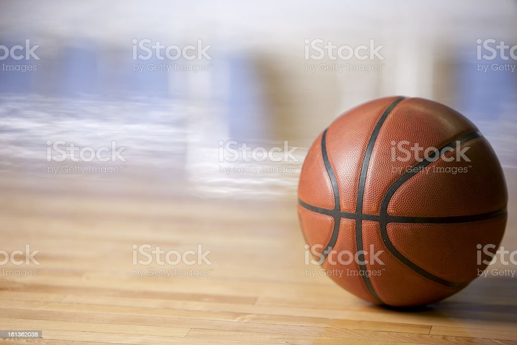 An unclaimed basketball sitting on the court floor royalty-free stock photo