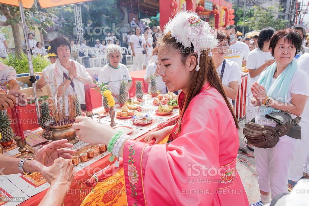 An unidentified devotee of a Chinese shrine blesses people stock photo