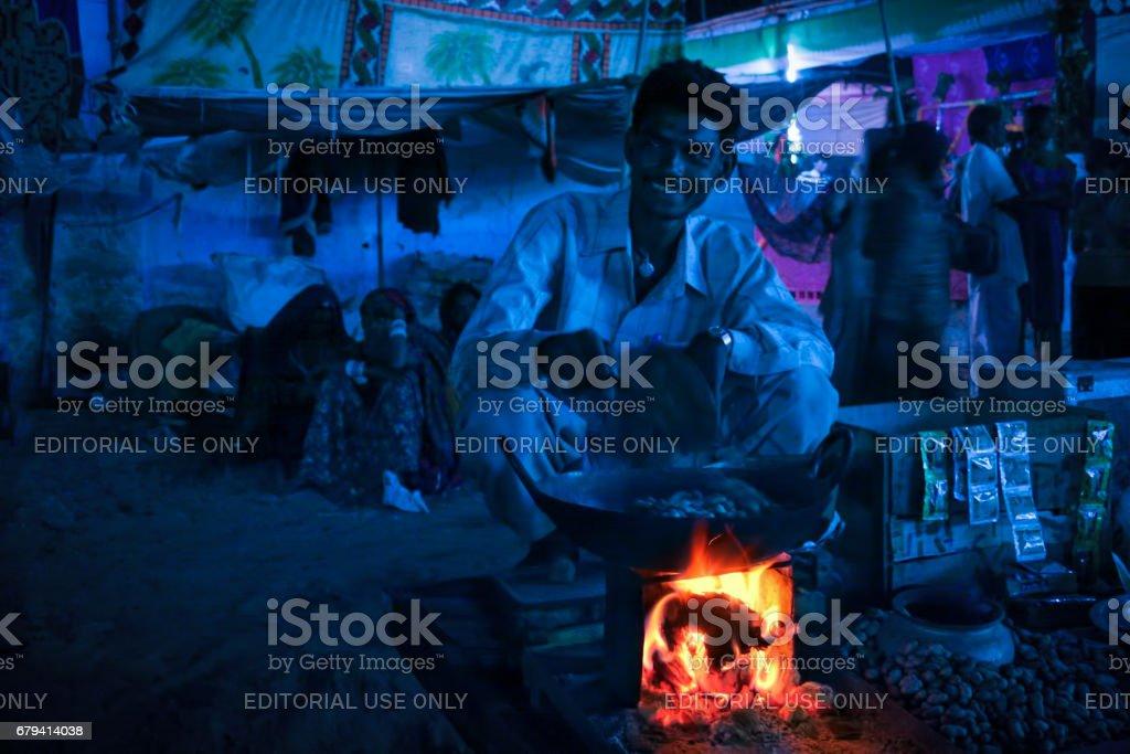An unidentified Indian Rajasthani man at his fair-side shop at annual Pushkar Camel Fair stock photo