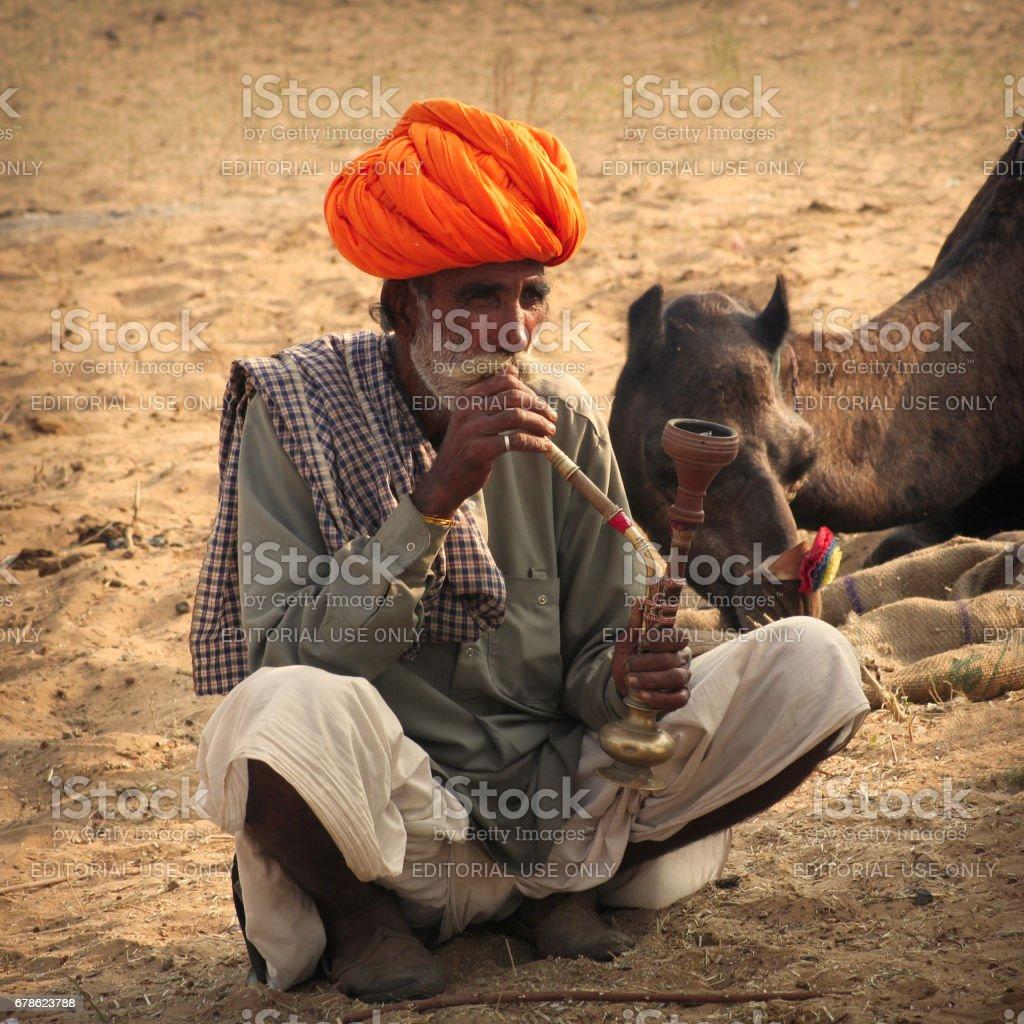 An unidentified Indian Rajasthani man in his rural attire smokes hukkah pipe at Pushkar Camel Fair stock photo