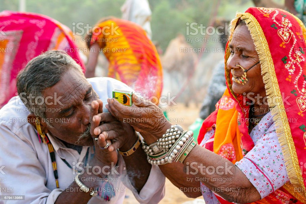 An unidentified Indian Rajasthani woman helps in igniting smoking pipe for her man at Pushkar Camel Fair stock photo