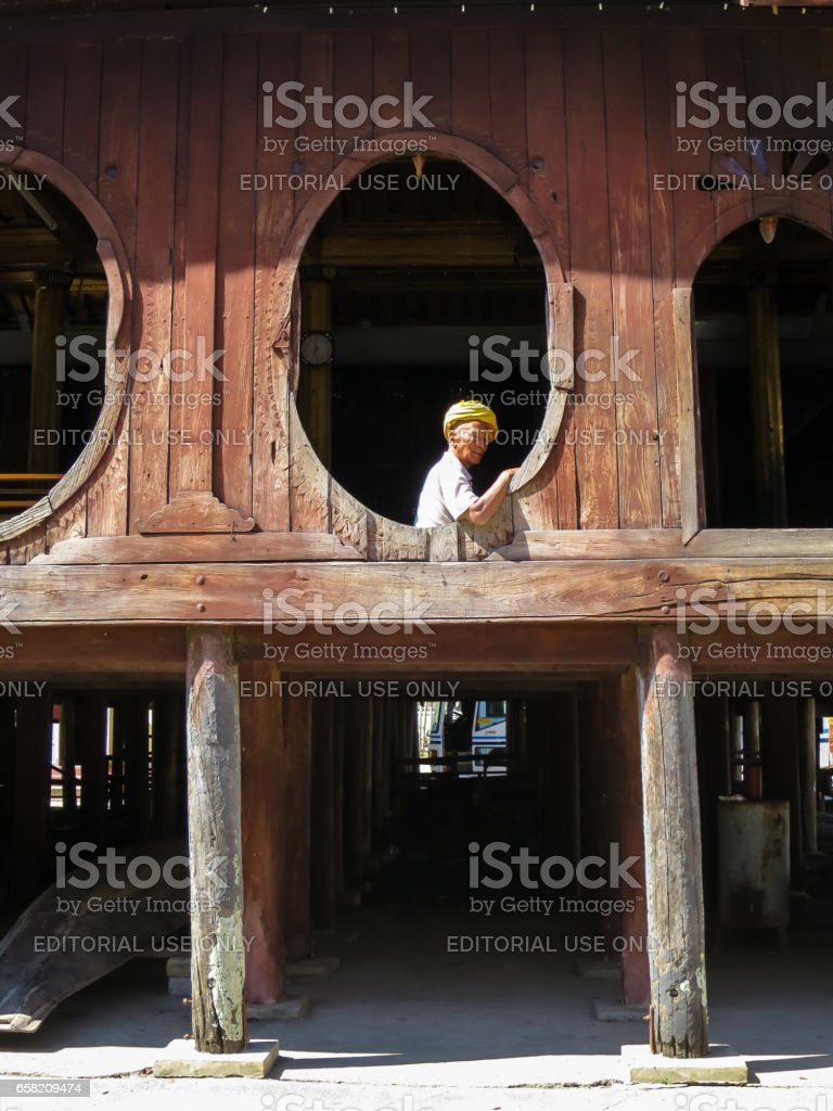 Nyaungshwe, Myanmar - January 24, 2015: An unidentified local old man wearing yellow turban looking out the unique oval window of Shwe Yaunghwe Kyaung monastery, Inle Lake, Nyaung Shwe, Myanmar. stock photo