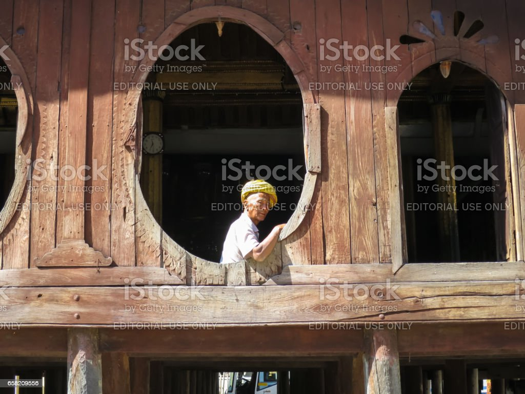 Nyaungshwe, Myanmar - January 24, 2015: An unidentified local old man wearing yellow turban sitting at the unique oval window of Shwe Yaunghwe Kyaung monastery, Inle Lake, Nyaung Shwe, Myanmar. stock photo