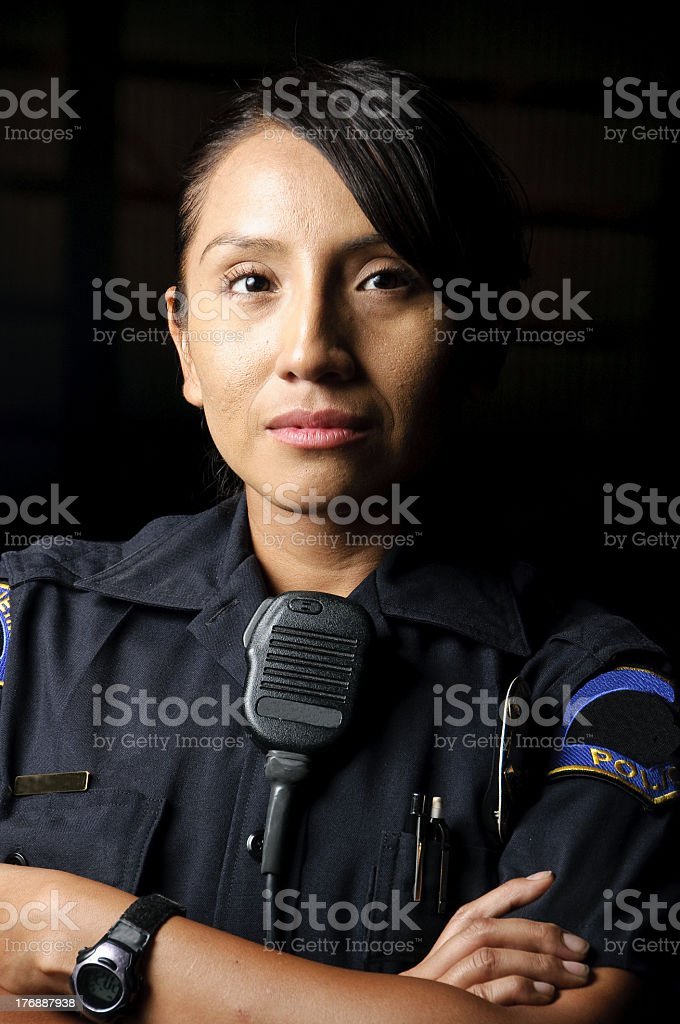 An uniformed female police officer with her arms folded stock photo
