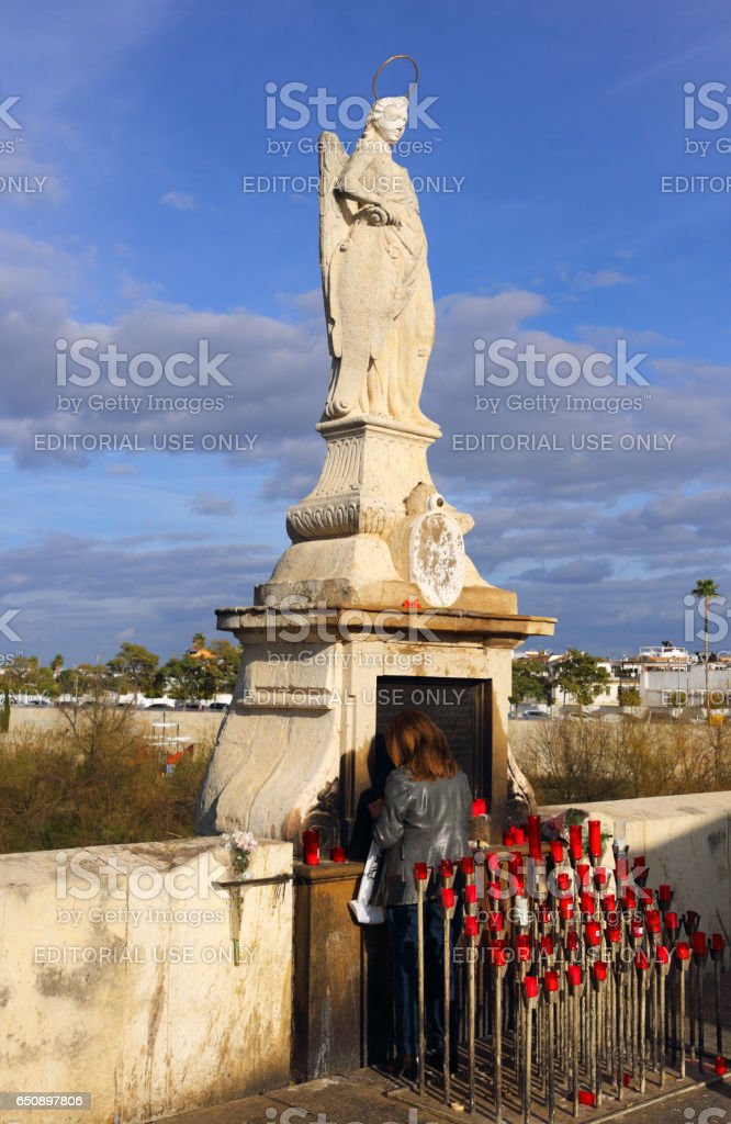 Cordoba, Spain - February 27, 2017: An unknown woman lights a candle at the statue of the Archangel Gabriel on the Roman Bridge which spans the Guadalquivir River. UNESCO World Heritage site and popular tourist attraction. stock photo