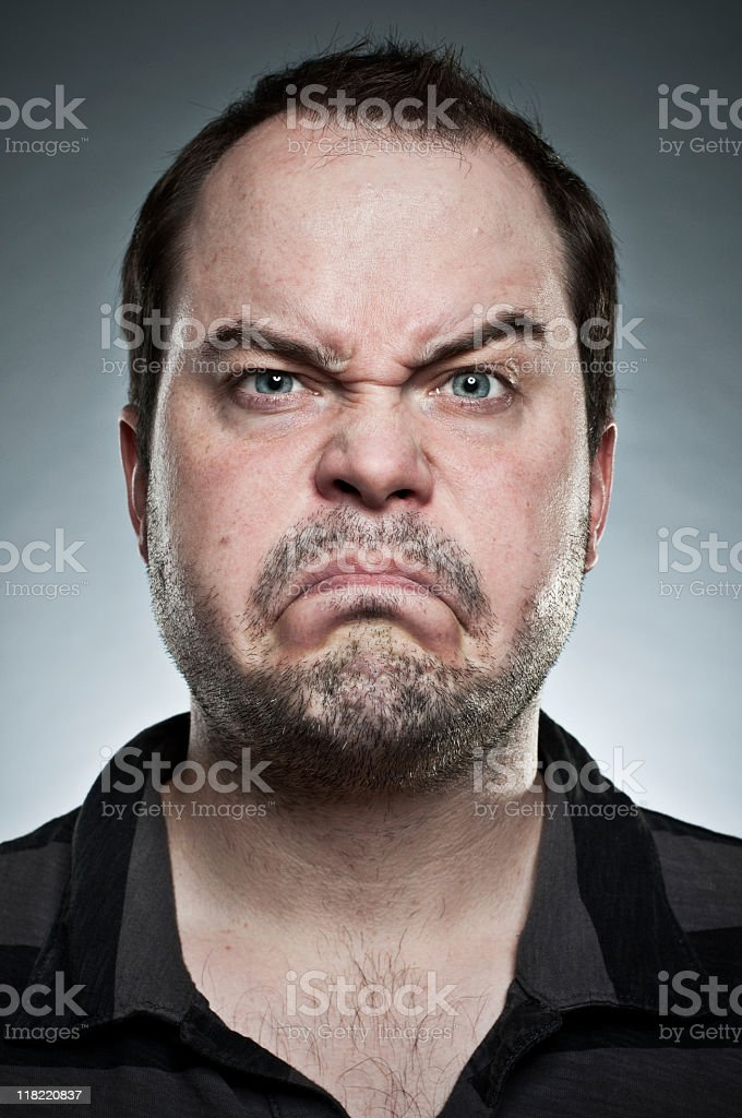 An unshaven man making a frown with eyebrows raised stock photo