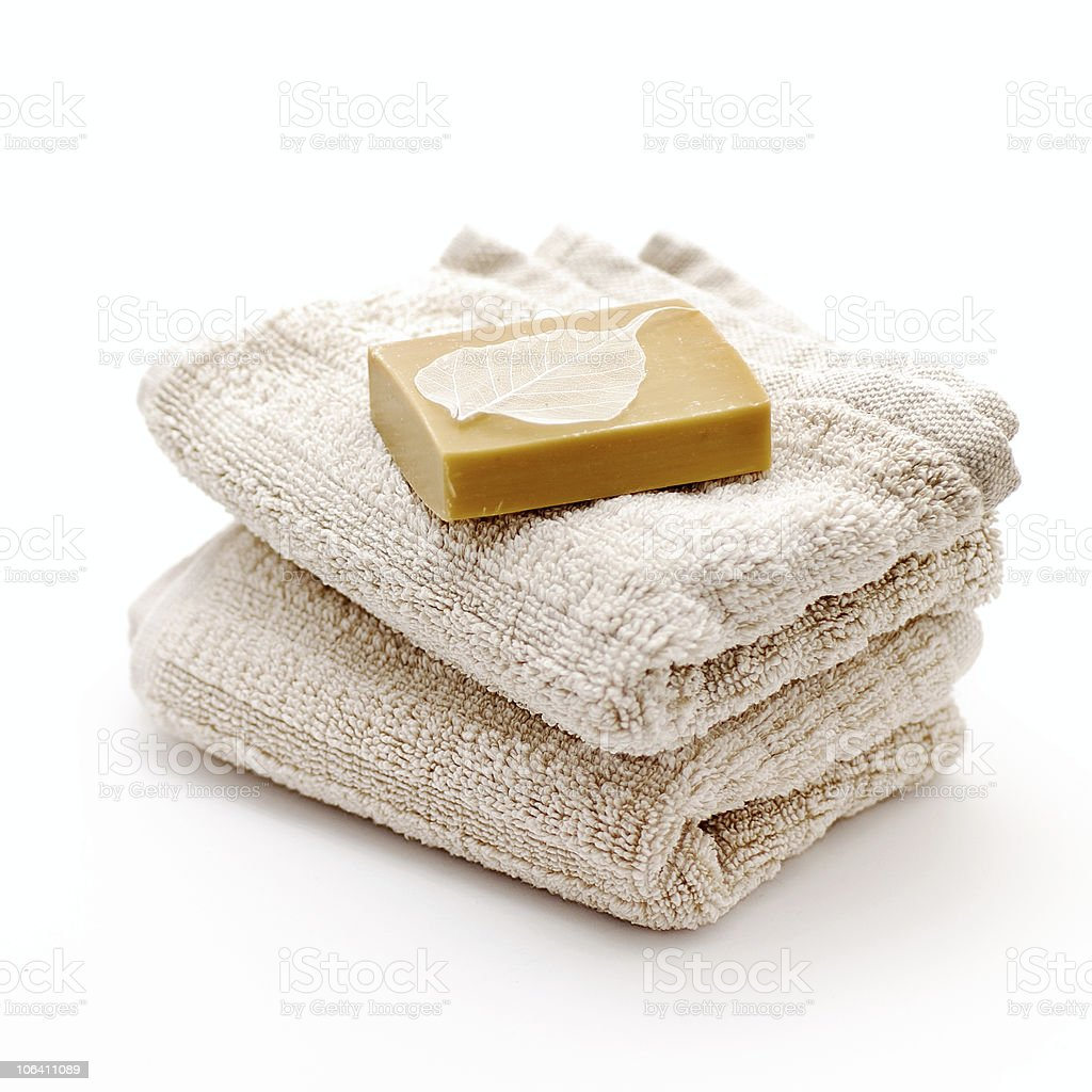 An unwrapped bar of soap atop two folded tan bath towels royalty-free stock photo