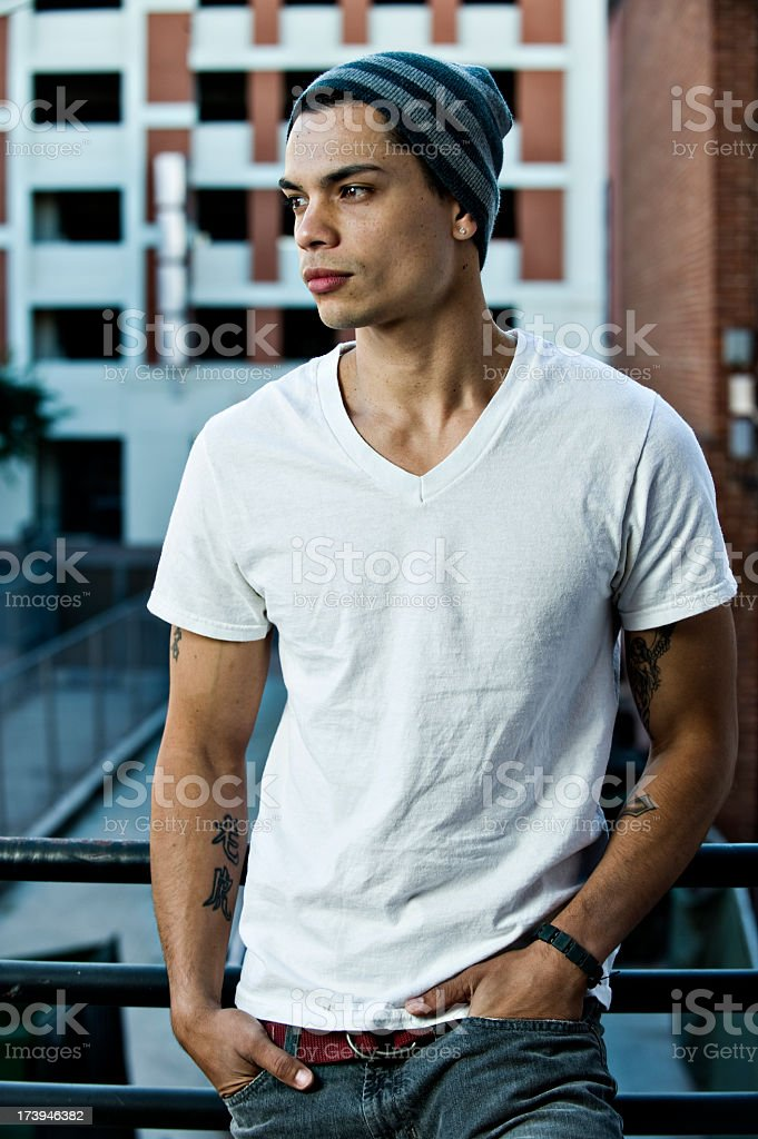 An urban man in a t-shirt and beanie posing in an alley royalty-free stock photo