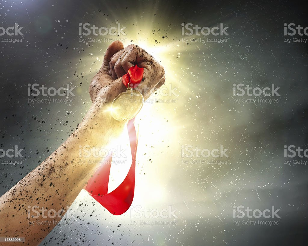 An winning athletes hand clutching a medal stock photo