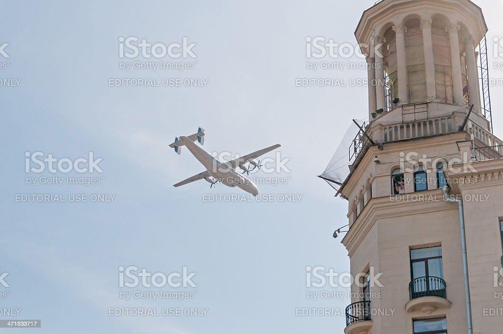 An-22 Antei aircraft passes by tower against sky background royalty-free stock photo