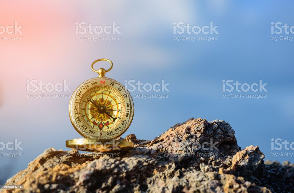 Analogical compass abandoned on the rocks with blurred sea background. stock photo