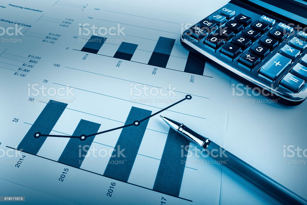 Analysing data, pen, calculator and graphs stock photo