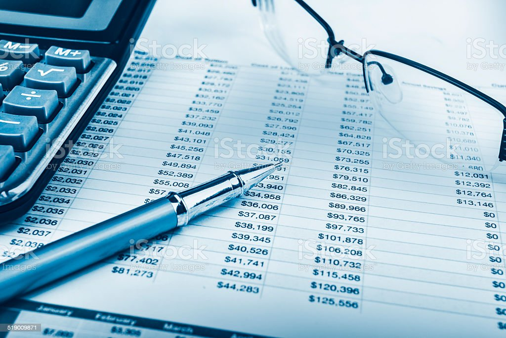 Analysing data, pen, calculator, spectacles and graphs stock photo