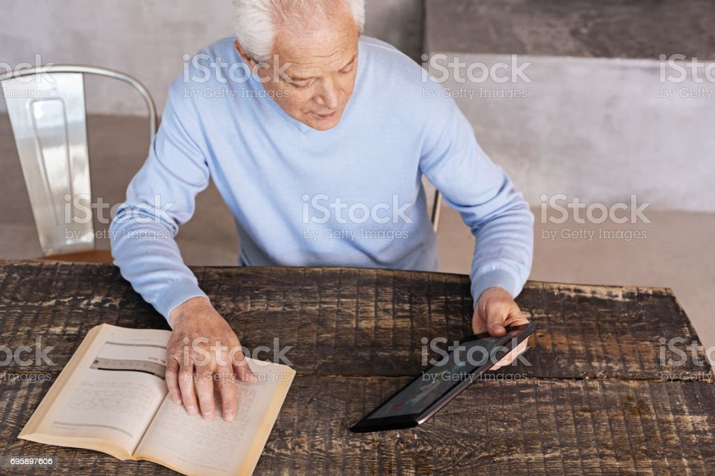 Analytical intelligent man choosing a better device stock photo