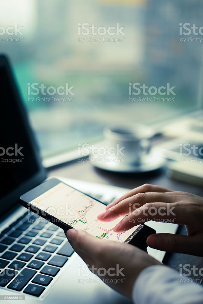 analyzing chart on mobile phone stock photo