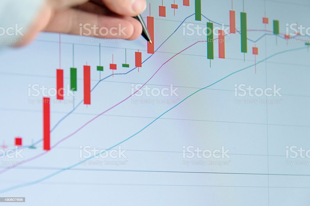 Analyzing data graphs on computer stock photo