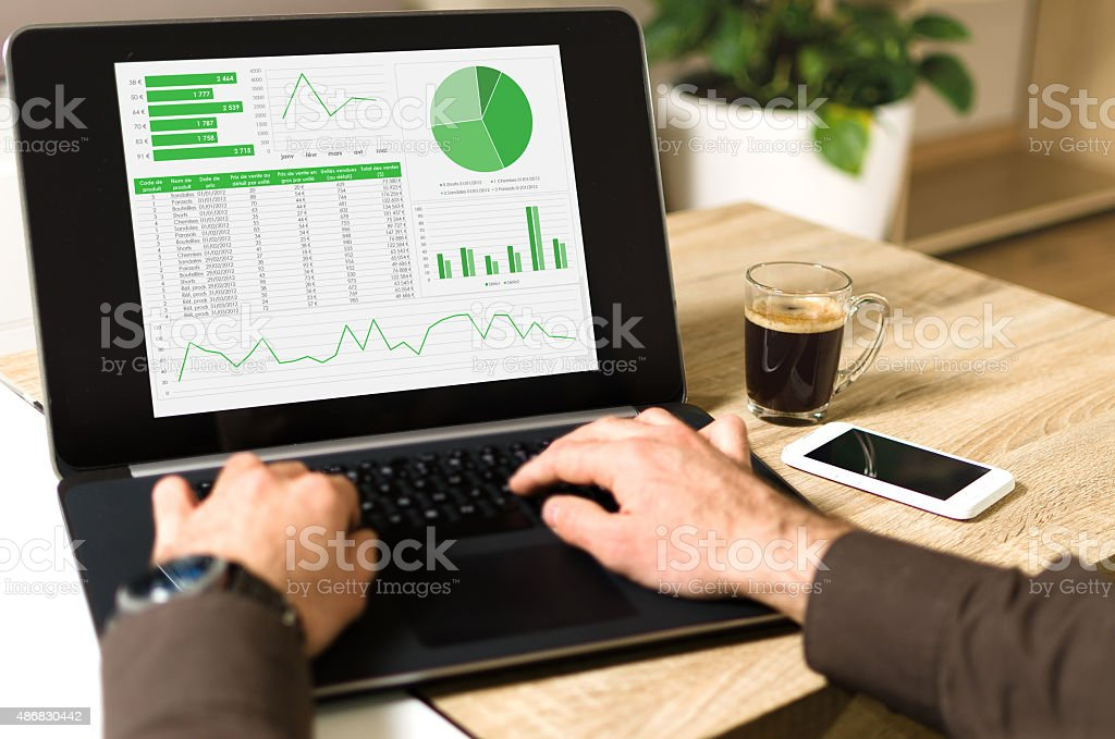 Analyzing data on a laptop computer (pov) stock photo