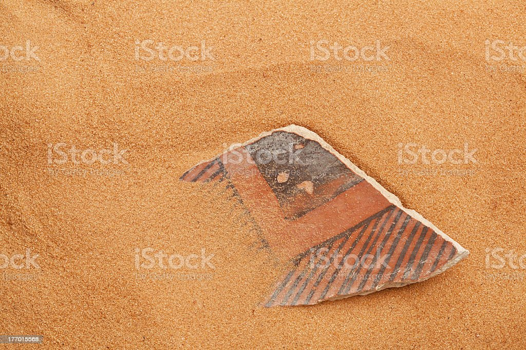 Anasazi pottery shard in red sand stock photo