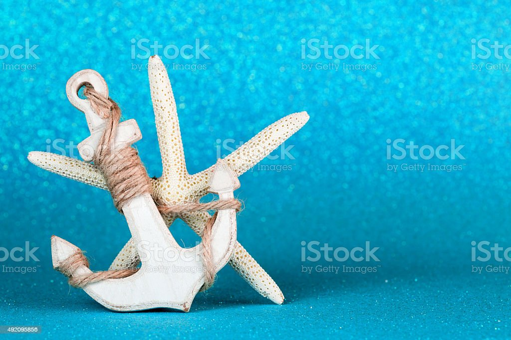 anchor and starfish in an azure sparkling backdrop stock photo