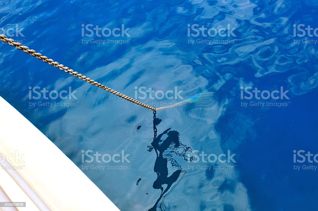 Anchor chain lowered into the blue water. stock photo