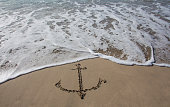 Anchor drawn in the sand on the beach
