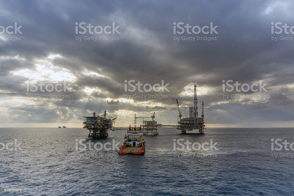 Anchor handling tugboat approaching oil rigs stock photo