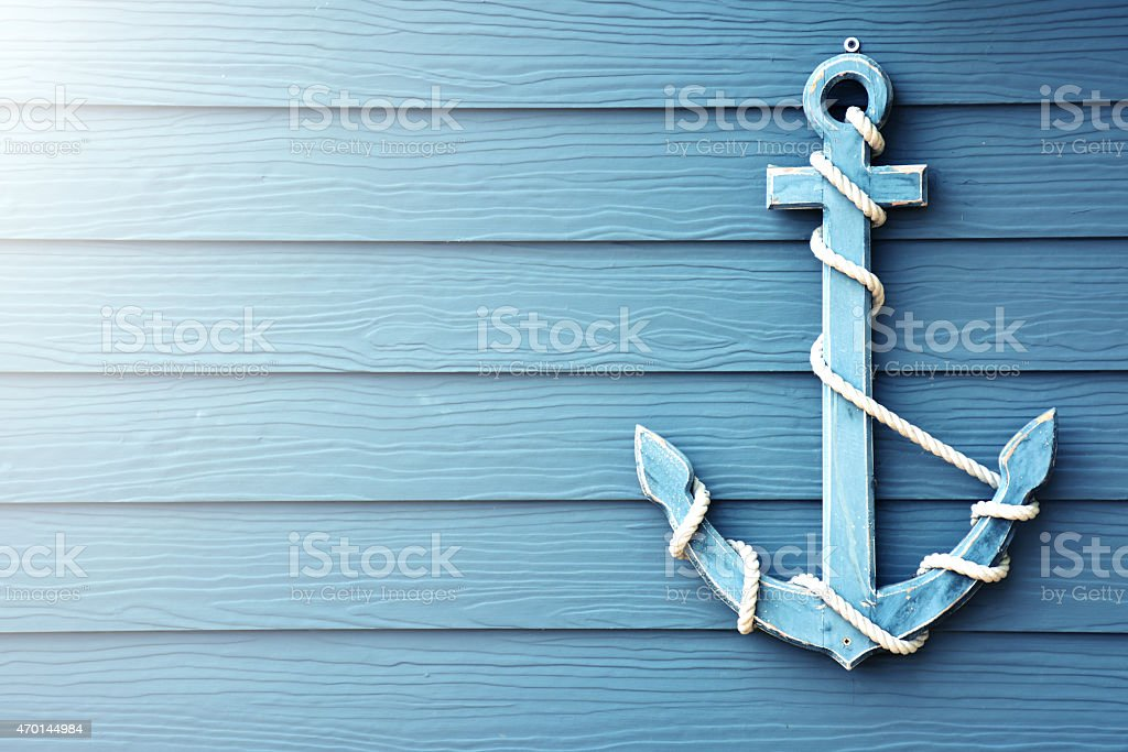 Anchor on blue wooden background. stock photo