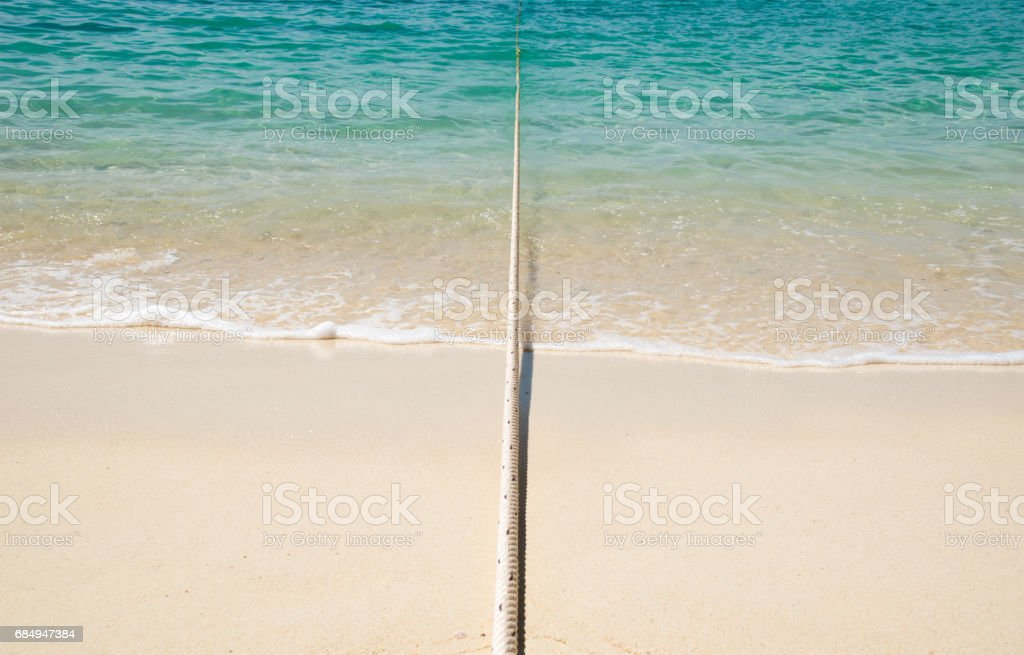 Anchor String rope from sea to beach stock photo