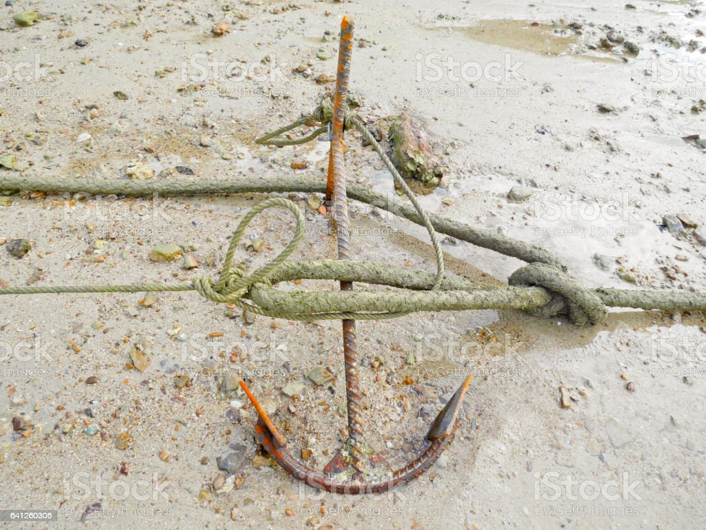 Anchor with barnacle lying on the beach stock photo