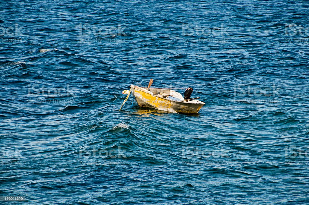 Anchored rowboat in ocean waves stock photo