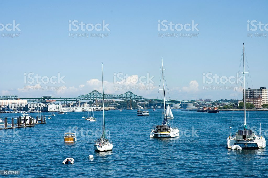 Anchored sailing boats and oil tankers stock photo