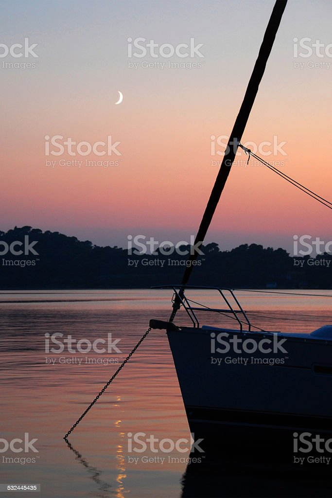 Anchored Yacht at Sunset with Moon stock photo
