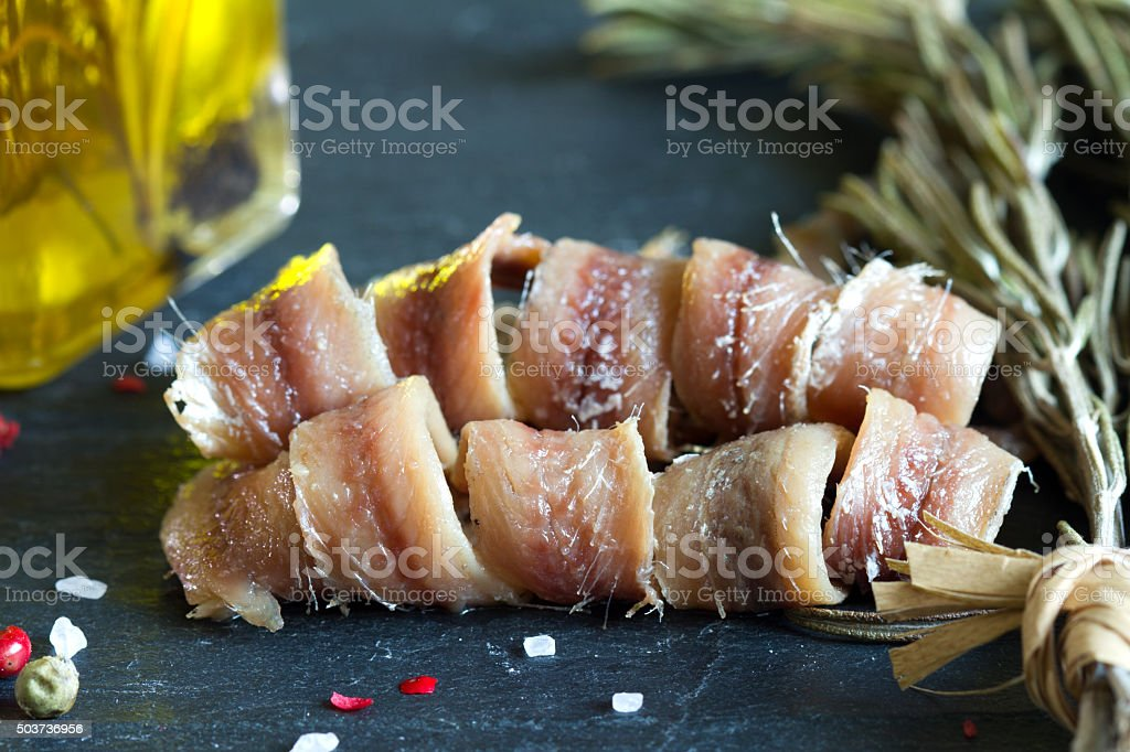 Anchovies with salt, oil and spices on black marble stock photo