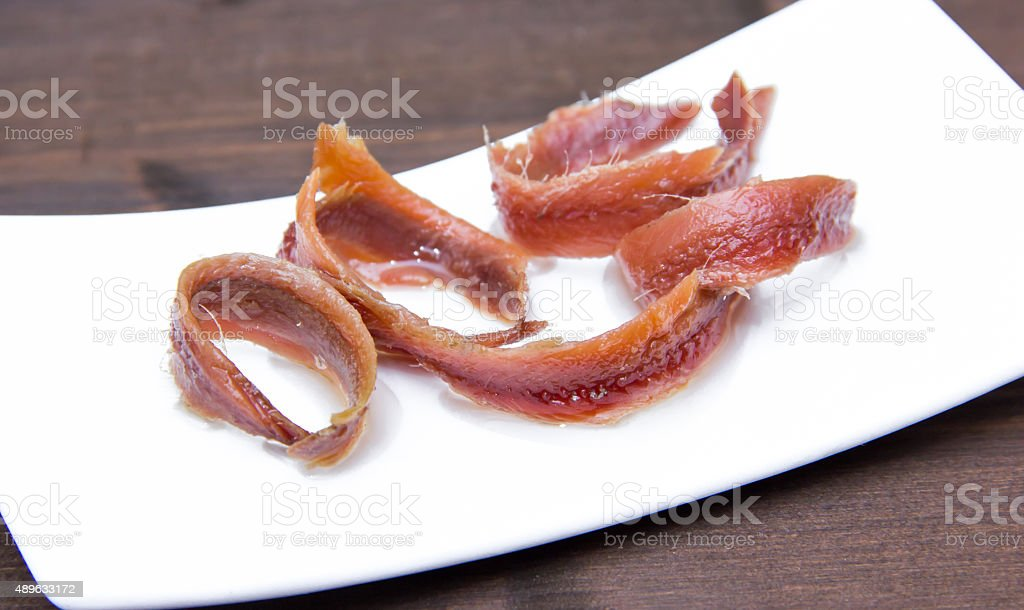 Anchovy fillets on tray on wood stock photo