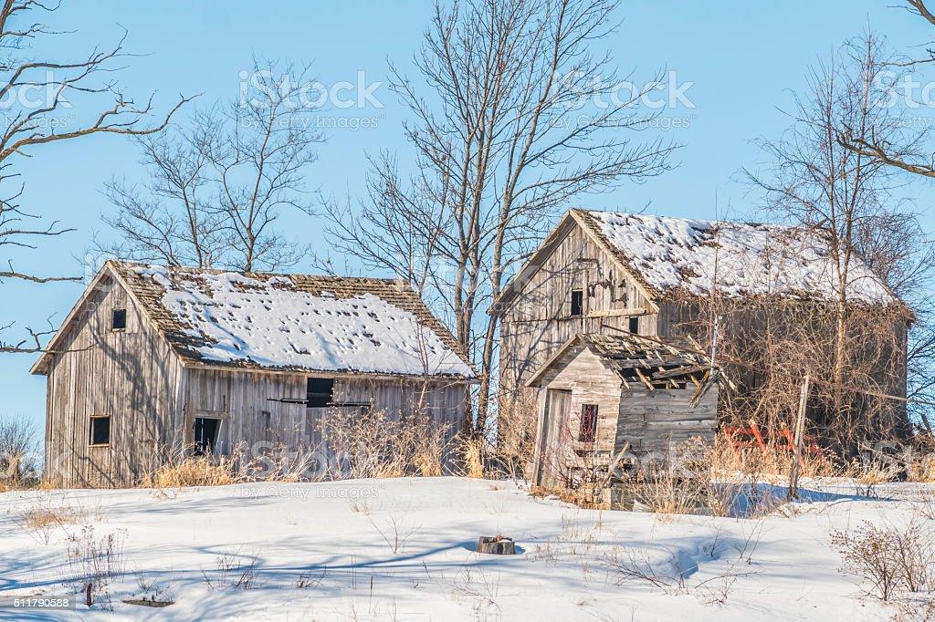 Ancient abandoned farm buildings adorn a rustic winter landscape stock photo