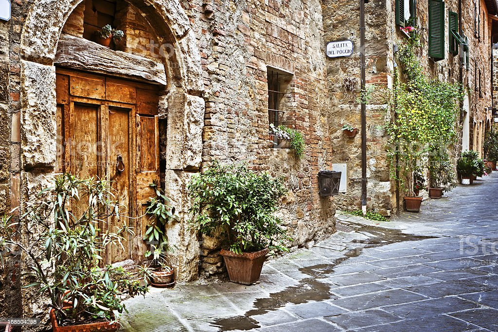 Ancient Alley with Wooden Door in Tuscan Village, Val d'Orcia stock photo