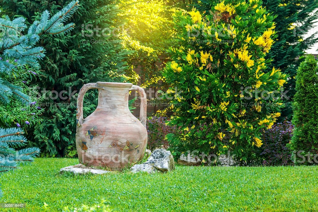 ancient amphora in garden stock photo