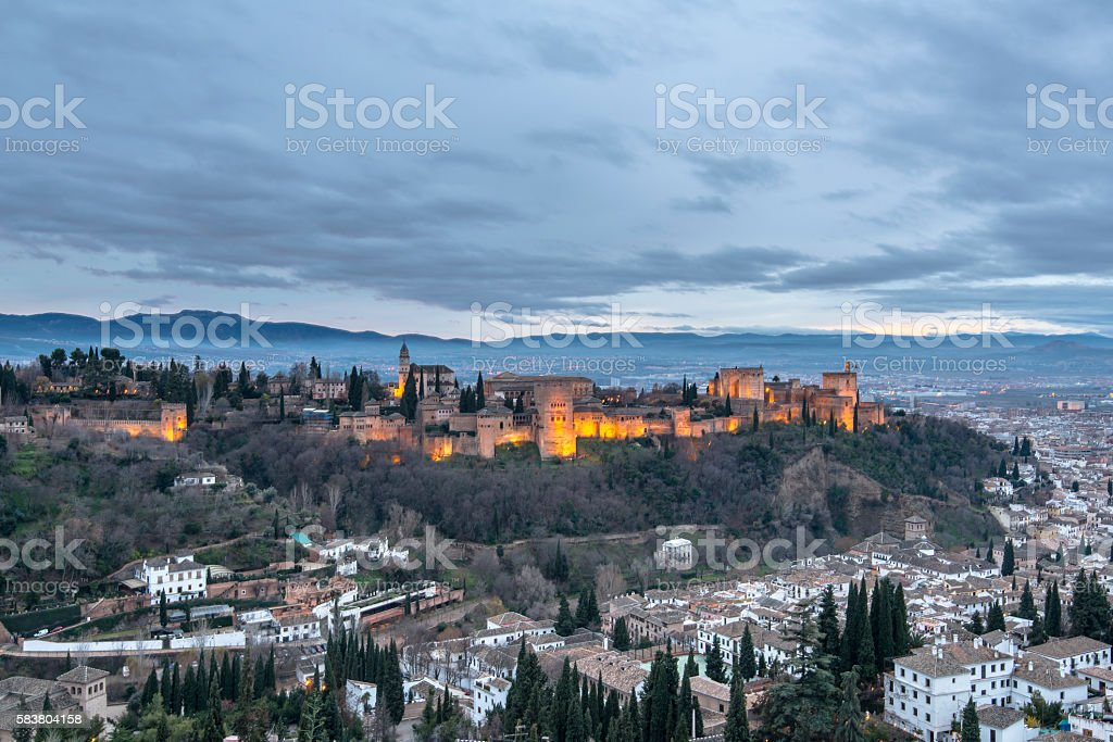 Ancient arabic fortress of Alhambra palace at dusk in Granada. stock photo